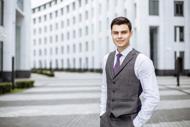 Retrato de hombre de negocios exitoso al aire libre en una ciudad moderna