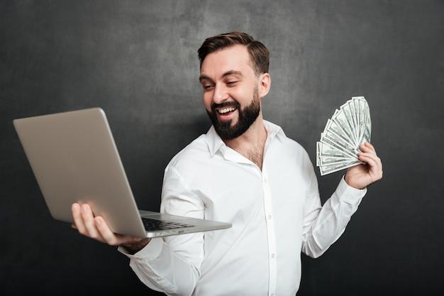 Retrato de hombre de negocios exitoso en camisa blanca con abanico de billetes de dólar de dinero y cuaderno de plata en ambas manos sobre gris oscuro