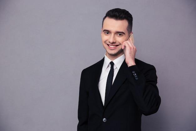 Retrato de un hombre de negocios feliz hablando por teléfono sobre pared gris