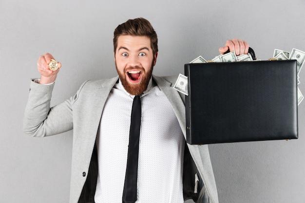 Retrato de un hombre de negocios feliz mostrando bitcoin dorado