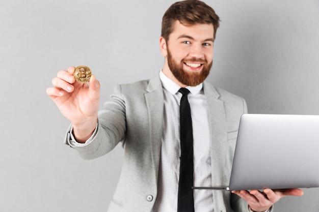 Retrato de un hombre de negocios feliz mostrando bitcoin