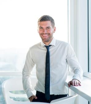 Retrato de un hombre de negocios feliz de pie en la oficina