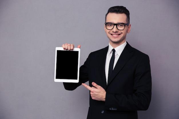 Retrato de un hombre de negocios feliz que muestra la pantalla de la tableta en blanco sobre la pared gris