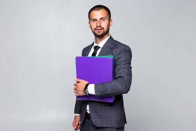 Retrato de un hombre de negocios feliz sosteniendo un cuaderno con documentos aislado sobre fondo blanco.