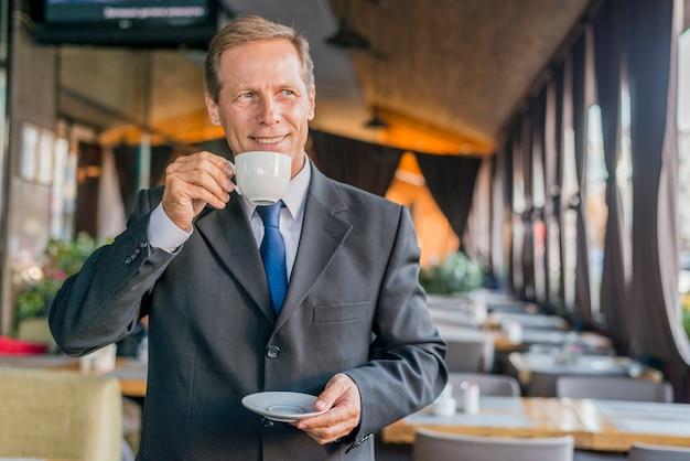 Retrato de un hombre de negocios feliz tomando café en el restaurante