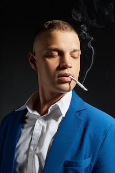Retrato de un hombre de negocios fumador en un costoso traje de negocios sobre un fondo oscuro