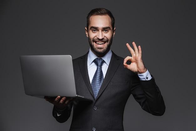 Retrato de un hombre de negocios guapo confiado vistiendo traje aislado, sosteniendo la computadora portátil, ok