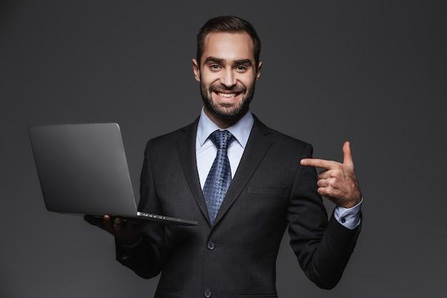 Retrato de un hombre de negocios guapo confiado vistiendo traje aislado, sosteniendo la computadora portátil