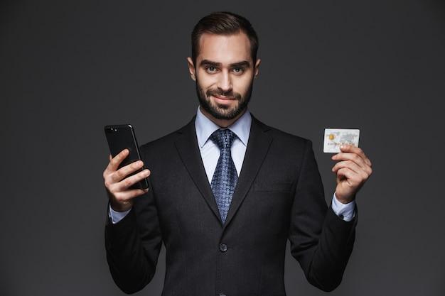 Retrato de un hombre de negocios guapo confiado vistiendo traje aislado, mediante teléfono móvil, mostrando tarjeta de crédito de plástico