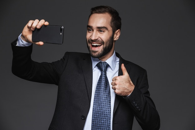 Retrato de un hombre de negocios guapo confiado vistiendo traje aislado, tomando un selfie