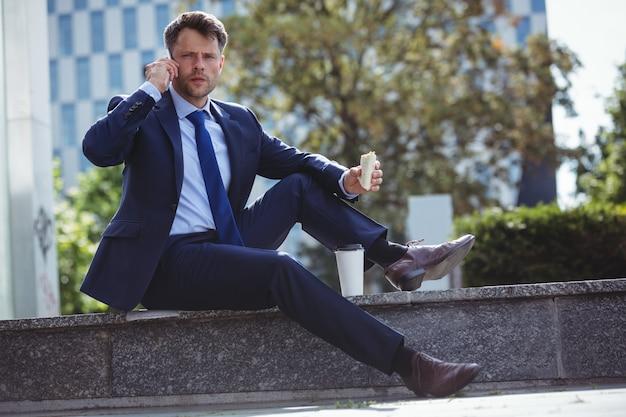 Retrato de hombre de negocios guapo hablando por teléfono móvil