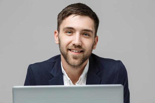Retrato hombre de negocios guapo jugando portátil digital con cara sonriente y confiada.