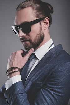 Retrato de hombre de negocios guapo modelo vestido con elegante traje azul con gafas de sol