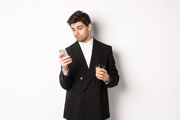 Retrato de hombre de negocios guapo pensativo, tomando café y navegando en internet, mirando la pantalla del teléfono inteligente, de pie contra el fondo blanco.
