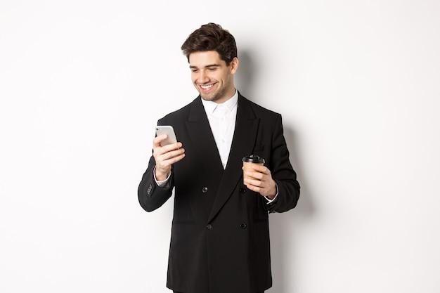 Retrato de hombre de negocios guapo y seguro en traje negro, tomando café y usando el teléfono móvil, sonriendo complacido, de pie sobre fondo blanco.