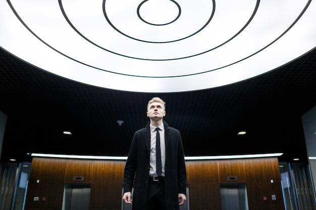 Retrato de hombre de negocios guapo en el vestíbulo de la oficina