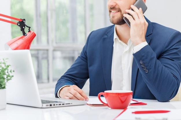 Retrato de hombre de negocios hablando por teléfono en la oficina