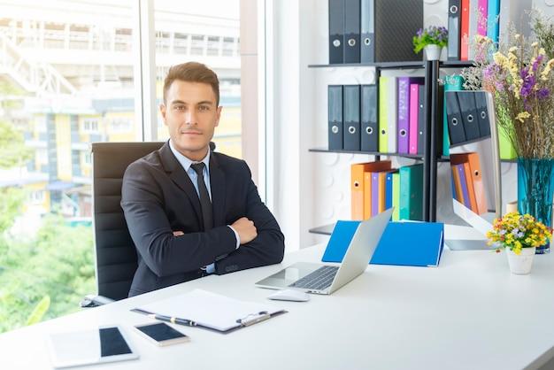 Retrato del hombre de negocios hermoso que se sienta con brazo-cruzado en oficina.
