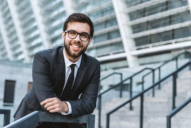 Retrato de un hombre de negocios del hombre joven con las lentes contra la perspectiva de un edificio de oficinas