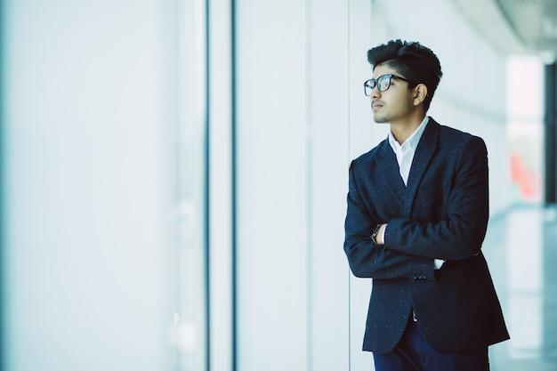 Retrato de hombre de negocios indio asiático sonriendo en la oficina moderna