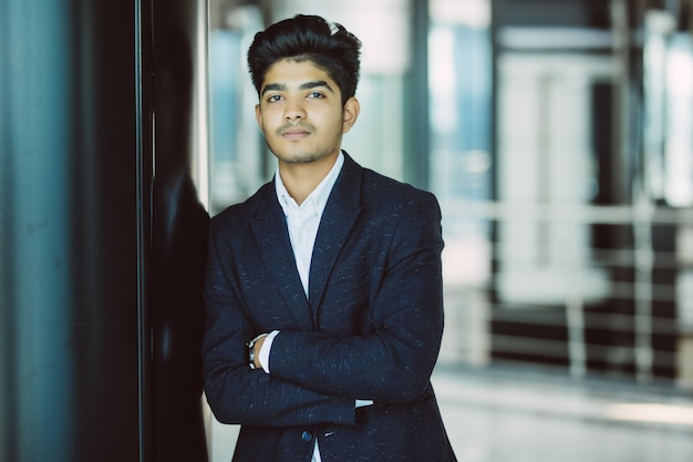 Retrato de un hombre de negocios indio feliz de pie en la sala de juntas