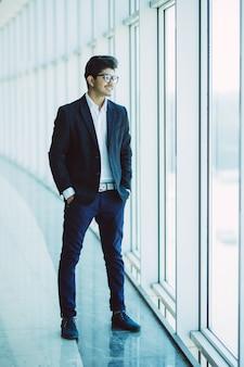 Retrato de hombre de negocios indio sonriendo en la oficina moderna