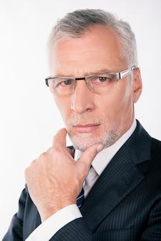 Retrato de hombre de negocios inteligente con barba gris reflexionando y poniendo su mano en la barbilla