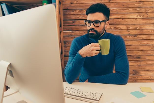 Retrato de hombre de negocios inteligente tomando café mientras trabaja en la computadora