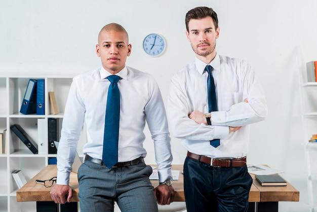 Retrato del hombre de negocios joven confiado dos que se coloca delante del escritorio en la oficina