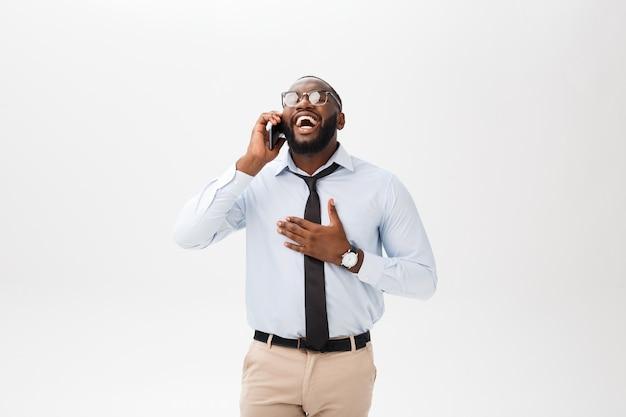 Retrato de un hombre de negocios joven confiado que habla en el teléfono celular