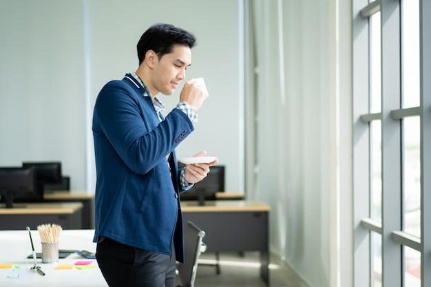 Retrato del hombre de negocios joven elegante y hermoso que bebe un café y que mira fuera de la ventana cercana para arriba.