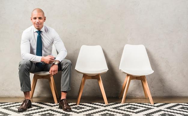 Retrato de un hombre de negocios joven feliz confiado que se sienta en silla delante de la pared gris