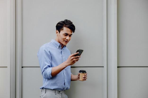 Retrato de un hombre de negocios joven feliz usando el teléfono móvil. estilo de vida de la gente moderna. de pie junto a la pared con una taza de café