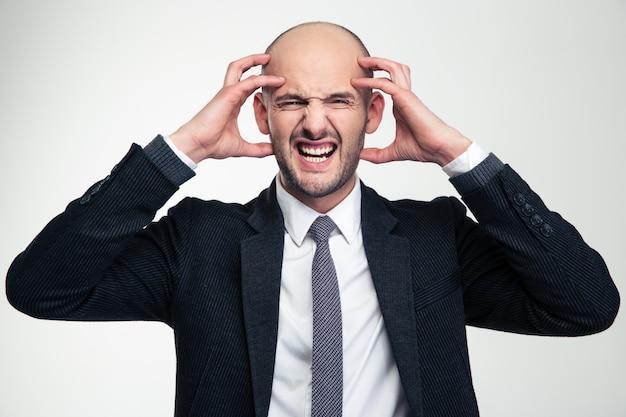 Retrato de hombre de negocios joven loco deprimido molesto en traje negro aislado sobre la pared blanca