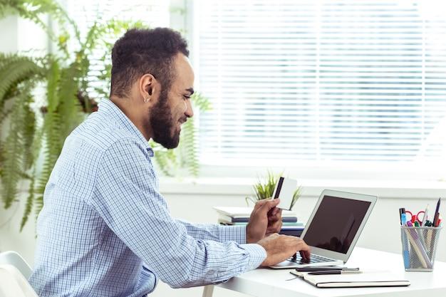Retrato de hombre de negocios joven negro africano guapo trabajando en la computadora portátil en la oficina