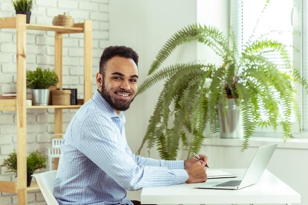 Retrato del hombre de negocios joven negro africano hermoso que trabaja en el ordenador portátil en la oficina