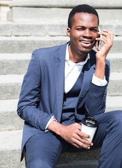 Retrato de un hombre de negocios joven que habla en los pasos que sostienen la taza de café disponible