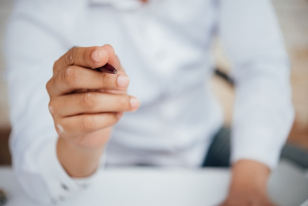 Retrato de hombre de negocios joven sentado en su escritorio