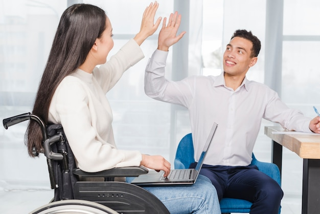 Retrato de un hombre de negocios joven sonriente que da el alto cinco a la mujer joven que se sienta en la silla de ruedas con el ordenador portátil