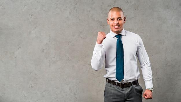 Retrato de un hombre de negocios joven sonriente que se opone a la pared gris que aprieta su puño