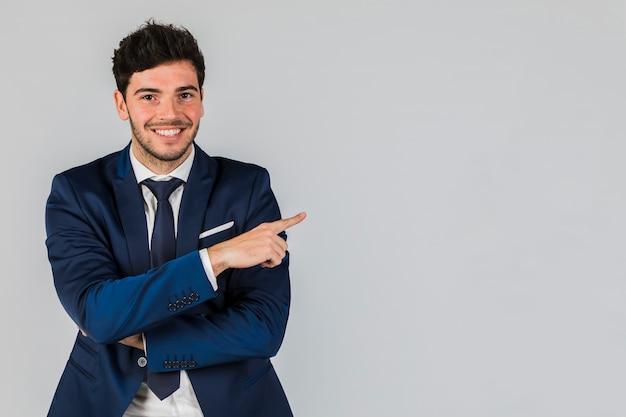 Retrato de un hombre de negocios joven sonriente que señala su dedo contra el contexto gris