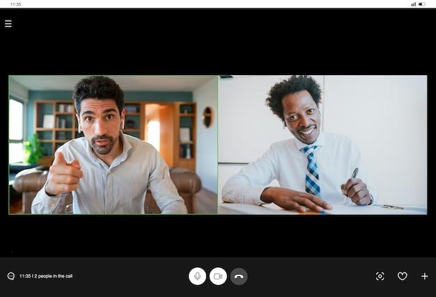Retrato de hombre de negocios joven en una videollamada de trabajo mientras se queda en casa