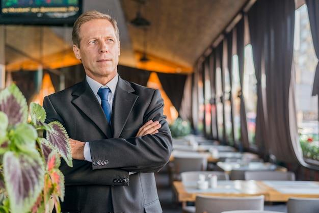 Retrato de un hombre de negocios maduro con los brazos cruzados de pie en el restaurante