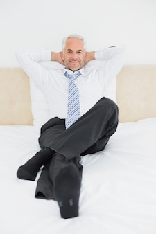Retrato de un hombre de negocios maduro relajado que se sienta en cama