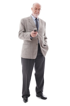 Retrato de hombre de negocios maduro con teléfono móvil aislado sobre fondo blanco.