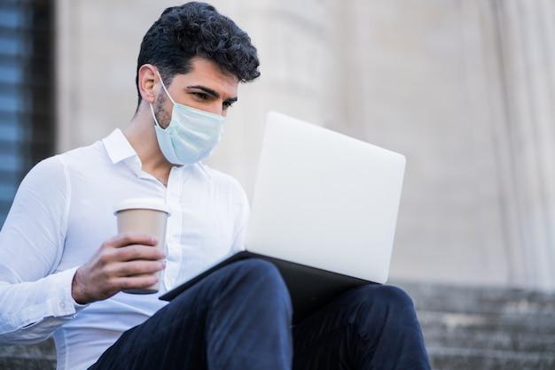 Retrato de hombre de negocios con mascarilla y usando su computadora portátil mientras está sentado en las escaleras al aire libre. concepto de negocio
