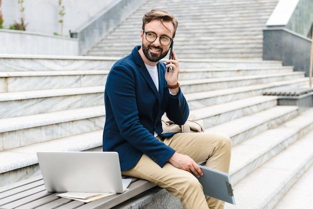 Retrato de hombre de negocios masculino con anteojos sosteniendo el portapapeles y hablando por teléfono celular mientras está sentado en un banco cerca de las escaleras