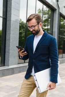 Retrato de hombre de negocios masculino con anteojos sosteniendo el portátil y escribiendo en el teléfono móvil mientras camina al aire libre cerca del edificio