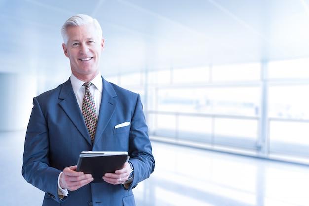 Retrato del hombre de negocios mayor que usa la tableta delante de su oficina moderna