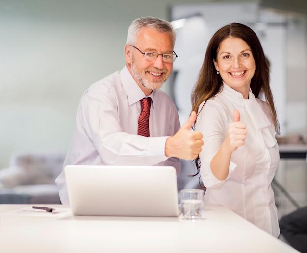 El retrato del hombre de negocios mayor sonriente y la empresaria que muestran el pulgar para arriba firman adentro la oficina